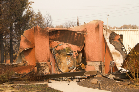 home severely burned with walls leaning and stucco hanging in the recent wild fire fire storm in Redding, California. Smoke and ash in the air as the fire continues to burn several miles away.