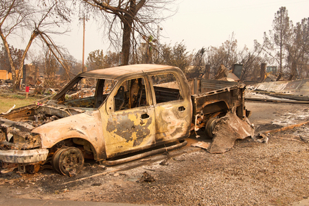 Charred truck in front of home burned to the ground in the recent wild fire fire storm in Redding, California. Smoke and ash in the air as the fire continues to burn several miles away. Stock Photo - 116310817