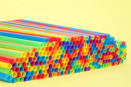 Hundreds of colorful plastic straws laying on yellow surface with yellow background facing open end at an angle towards viewer. Many cities are now banning single use plastic straws.