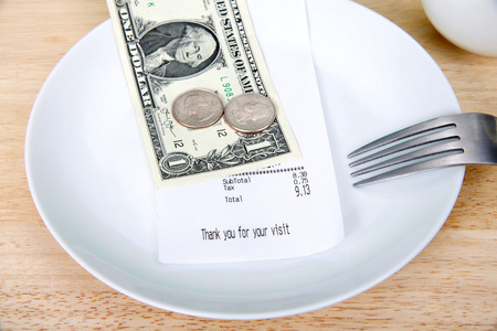 Plate with fork upside down indicating finished with meal, mug beside, bill receipt on plate. For mathematically challenged patrons, double the tax to calculate roughly how to leave for gratuity.