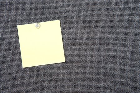 Note paper on grey fabric peg board held in place with clear tack. Copy space on paper note square and background.