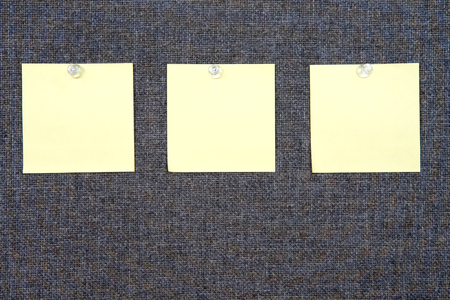 Three Note papers on grey fabric peg board held in place with clear tacks. Copy space on paper note squares and background.