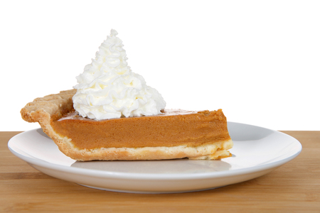 Slice of fresh pumpkin pie on a white porcelain plate heaped high with whipped cream on a wood table isolated on white background. A holiday favorite.