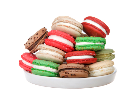 many Christmas holiday style macaron cookies stacked on a plate isolated on white. Minimalist design.
