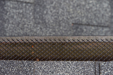 Close up on section of rain gutter residential home, free of leaves and debris, covered with mesh, which helps to keep leaves and debris out of rain gutters to improve functionality prevent damage.