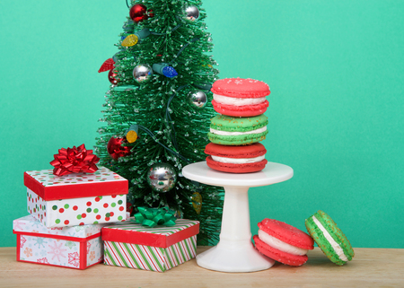 Christmas holiday style macaron cookies stacked on a pedestal and laying on wood table with light green background with colorful presents and small Christmas tree.