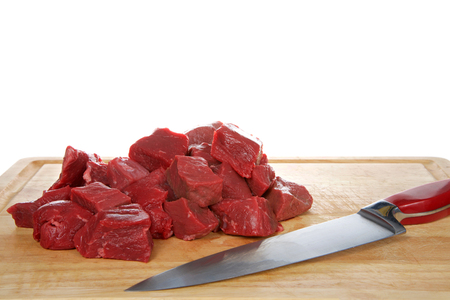 Fresh chopped beef steak chunks on wood chopping board with knife laying in front of meat, isolated on white background Reklamní fotografie