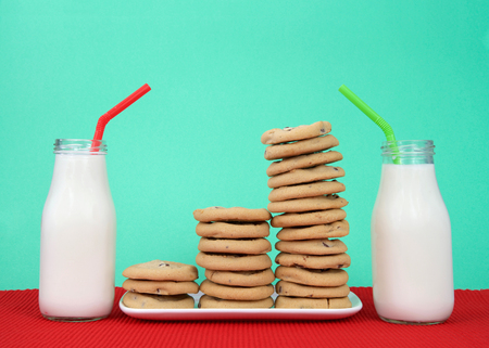 Chocolate chip cookies stacked at multiple heights on a white rectangular plate red placemat, green background. Two bottles of milk next to plate with red and white stripped straws
