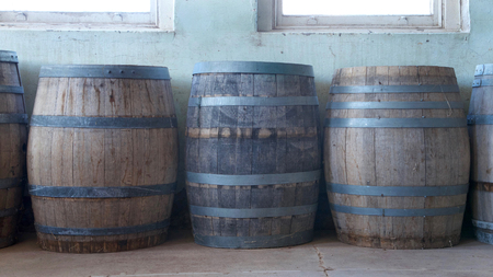 Old wood barrels lining a worn weathered wall in the basement of an old building. Used for food storage in early American history Stock Photo