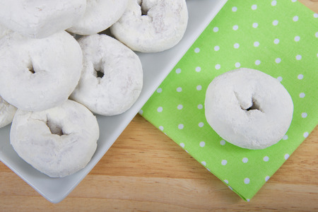 cropped angle view of a square plate with round powdered donuts on a light wood table, one donut isolated on green cloth napkin with white polka dots