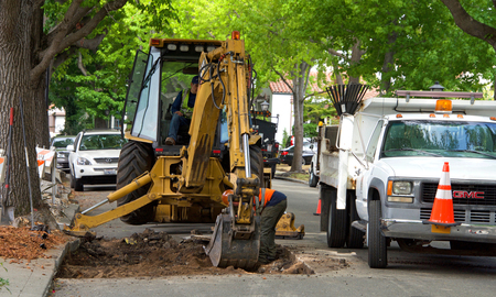 Alameda, CA - July 11, 2018: County work crew repairing roads damaged by tree roots. Root heave, sometimes called pavement heave, is triggered by tree roots that do not have sufficient growing space.