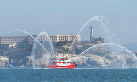 San Francisco, CA - October 05, 2018: Fireboat 3 leading the Parade of Boats at the 37th annual Fleet week, Alcatraz in the background. The vessel has an 18,000 gallon per minute pumping capacity. 報道画像