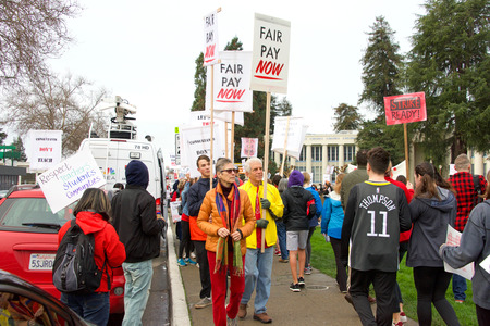 Oakland, CA - January 18, 2019: Oakland teachers having a one day sick out to protest slow progress on contract talks with the district. Fighting for smaller class sizes and bigger paychecks.