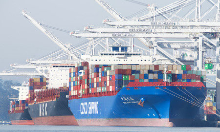 Oakland, CA - January 03, 2018: Cargo Ships loading at the Port of Oakland which discharges more then 99 percent of containerized goods moving through Northern California.