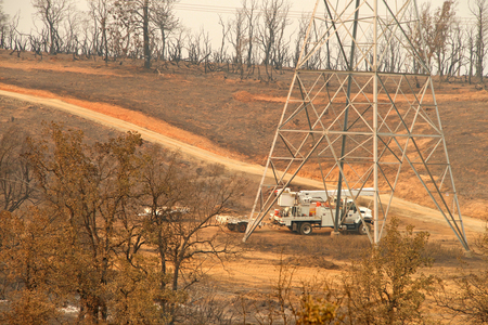 Redding, CA - August 06, 2018: PG and E crew working on the power lines in fire decimated area in the wake of the Carr fire. Smoke and ash in the air as the fire continues to burn several miles away. Banque d'images - 116659792