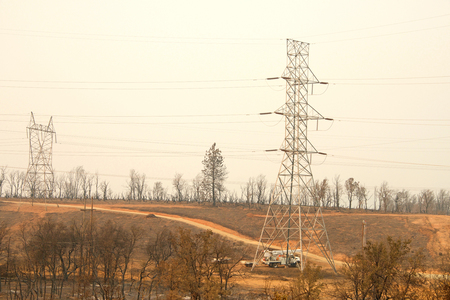Redding, CA - August 06, 2018: PG and E crew working on the power lines in fire decimated area in the wake of the Carr fire. Smoke and ash in the air as the fire continues to burn several miles away. Banque d'images - 116659840