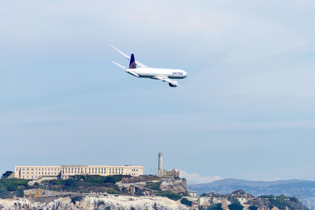 San Francisco, CA - October 05, 2018: United Airlines passenger plane performing in the 37th annual Fleet Week Air Show in San Francisco, CA.  Alcatraz seen below the flight path. Stok Fotoğraf - 116659843
