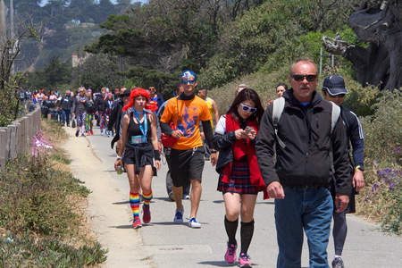 San Francisco, CA - May 20, 2018: Unidentified participants in the 107th annual Bay to Breakers race approaching the finish line. Bay to Breakers is well known for many participants wearing costumes.