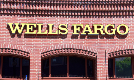 San Francisco, CA - April 01, 2018: Wells Fargo bank sign on a brick building. Wells Fargo and Co is an American multinational financial services company headquartered in San Francisco, CA