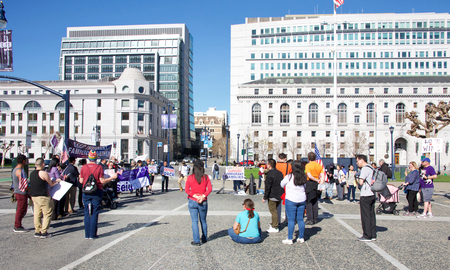 San Francisco, CA - February 03, 2018: A handful of participants participating in a March for Immigrants rally and march at Civic Center, downtown San Francisco.