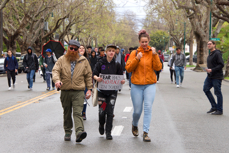 """Alameda, CA - March 14, 2018: With calls to """"End gun violence, no more silence!� hundreds of students from Alameda High School participate in a student walkout to protest gun violence as it starts raining. Editorial"""