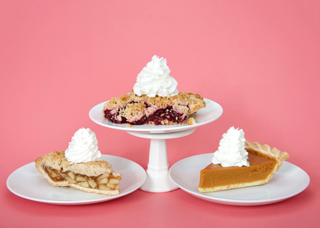 Apple and pumpkin pie on plates with whipped cream, cherry pie on plate with whipped cream on pedestal above them. Pink background. National pie day march 14 Stock Photo