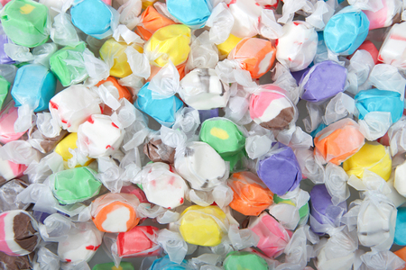 Background of salt water taffy in various flavors and colors wrapped in white transparent paper. Salt water taffy is sold widely on the boardwalks in the U.S. and Canada.