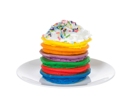 Stack of bright colorful pancakes topped with whipped cream and candy sprinkles. Fairy pancakes for National International Pancake day. Isolated on white.
