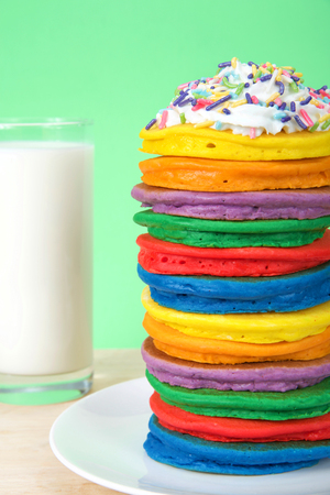 Stack of bright colorful pancakes topped with whipped cream and candy sprinkles with green background and glass of milk. Vertical presentation, Fairy pancakes for National International Pancake day.