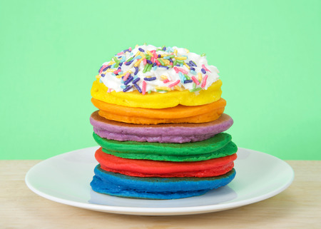 Stack of bright colorful pancakes topped with whipped cream and candy sprinkles with green background. Fairy pancakes for National International Pancake day. 写真素材