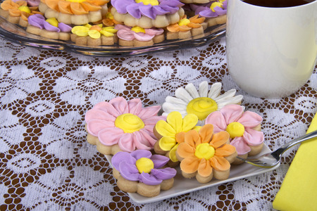 Fancy and elegant home made spring flowers sugar cookies with royal icing petals piped on. served on a plate with beverage of choice, coffee or tea. Plate of cookies in background on glass plate.
