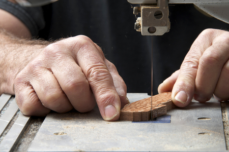 Male hands holding a small piece of wood precision cutting on a table top jig saw. Saw dust everywhere. 版權商用圖片