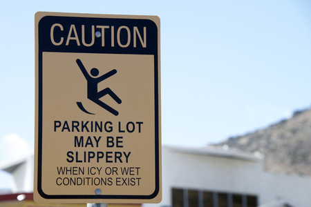 Caution, Slippery when wet sign in a parking lot. Warning patrons