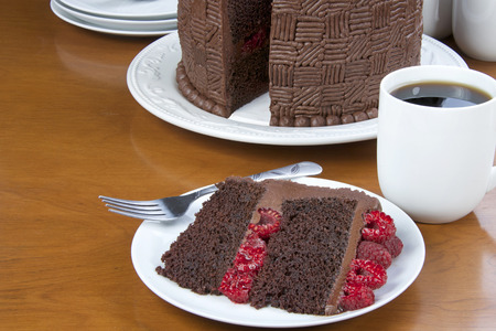 Slice of Home made original design chocolate cake with fresh raspberry filling and raspberries on top served on a plate with whole cake in the background. Plates, forks, cups. coffee on a wood table