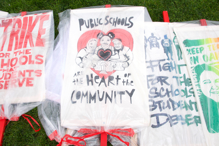 Oakland, CA - February 25, 2019: Signs covered in plastic to protect from the rain for the Oakland teachers strike day 3 rallying at Frank Ogawa Plaza. Fighting for smaller class sizes and bigger paychecks. Editorial