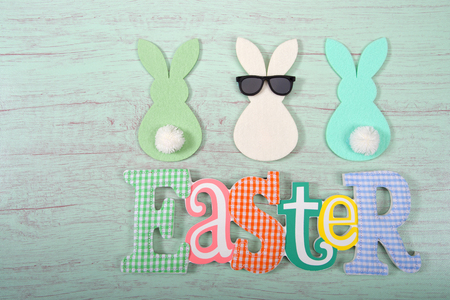 Felt bunnies in earth tone colors in a row, middle bunny wearing fun sunglasses other bunnies bottoms forward. Easter sign below. Hoppy Easter theme.
