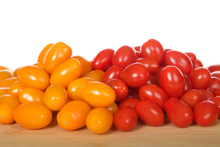 Zima, an orange grape tomatoes next to Angel Sweet grape Tomatoes. Both great for salads or snacking.