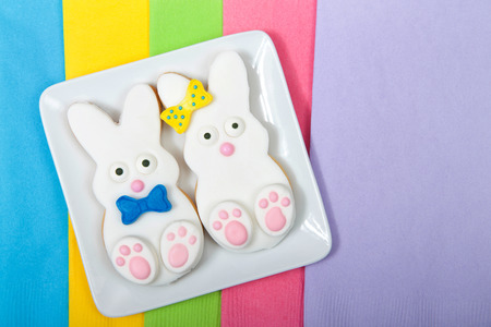 Easter Bunny Sugar Cookies on a square plate with napkins underneath. Marshmallow fondant covered cookie with candy feet, eyes and nose and tail and bows. Boy and girl.