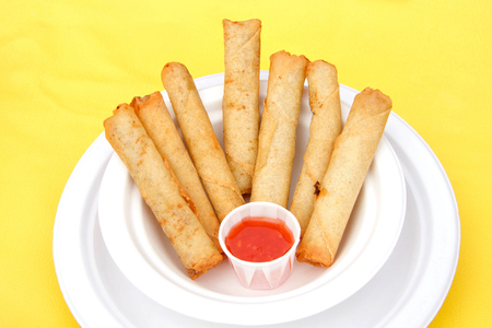 White paper plate with lumpia and dipping sauce on yellow table cloth. Popular street fair food. Stok Fotoğraf