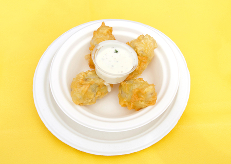White paper plate with battered and fried artichoke with dipping sauce on a yellow table cloth. Popular street fair food. Stok Fotoğraf