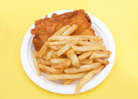 White paper plate with fish and chips on yellow table cloth. Popular street fair food.