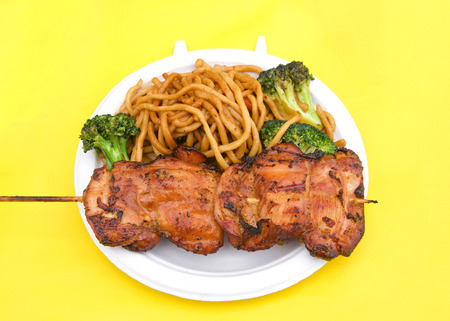 White paper plate with teriyaki chicken on skewer with chow mein noodles on yellow table cloth. Popular street fair food. Stok Fotoğraf