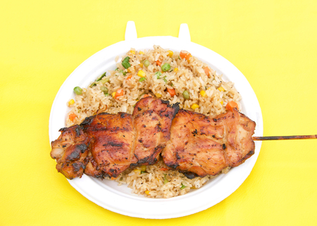 White paper plate with teriyaki chicken on skewer with fried rice on yellow table cloth. Popular street fair food.