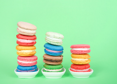 Macaron cookies in tiny white dishes stacked in graduated rows, colorful traditional french pastry on a mint green background.