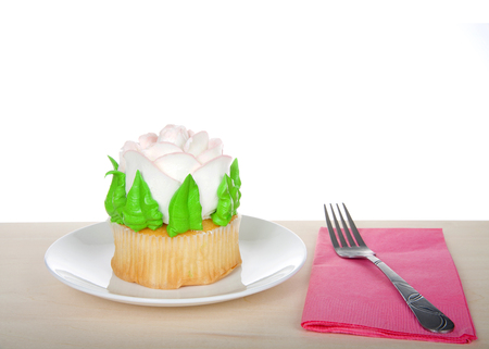 Large cup cake with giant frosting rose sitting on white plate on wood table, pink napkin with fork. Simple design with copy space for Mothers Day, Valentines Day, Quinceanera or birthday