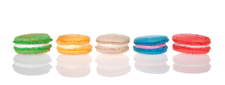 Row of macaron cookies laying sideways side by side multiple colors and flavors on a reflective surface isolated on white. Traditional french treat. Stok Fotoğraf