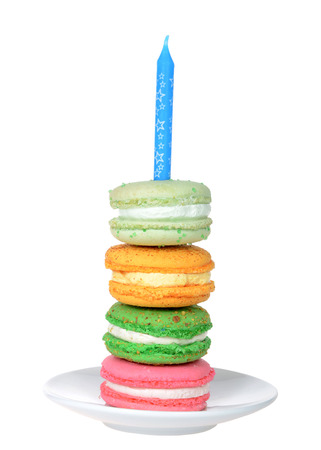 Stack of colorful macaron cookie with cream filling on a white plate with blue candle Isolated on white. Birthday party theme.