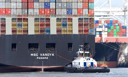 Oakland, CA - May 20, 2019: Tugboat DR HANK CAPLAN at the stern of cargo ship MSC VANDYA, assisting the vessel to manuever out of the Port of Oakland