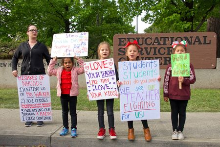 Union City, CA - May 22, 2019: Young students holding signs in front of the New Haven School District Educational Services Center in protest. The 1st teachers strike ever at New Haven Unified's scho