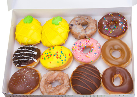 Top view flat lay of one dozen various plain and fancy donuts in a white box isolated. Are donuts becoming a new fad or the new trend. Gourmet style fancy donuts. Stok Fotoğraf